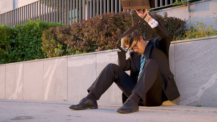 Young man sits on the pavement and strikes his briefcase after getting fired.