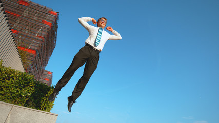 LOW ANGLE: Athletic businessman jumps high in the air after successful meeting.