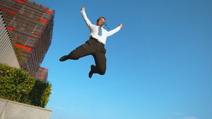 LOW ANGLE: Happy businessman celebrates finishing work before going on vacation.