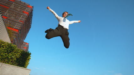 LOW ANGLE: Corporate professional jumps off the ledge and high into the air.