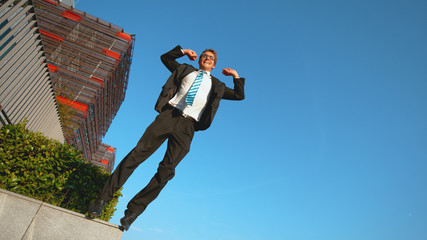 LOW ANGLE: Smiling Caucasian businessman jumps off ledge with arms outstretched.