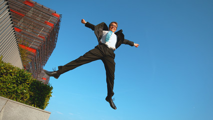LOW ANGLE Ecstatic Caucasian businessman jumps in the air with arms outstretched