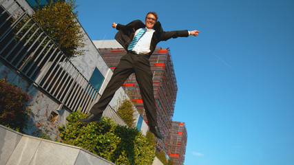 LOW ANGLE: Excited businessman jumps off the ledge and outstretches his arms.