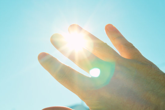 Male hand covers the sun. The sun shines through the palm. Scorching sun. Background. Texture.
