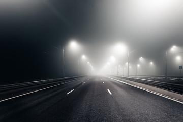 Foggy misty night road illuminated by street lights Fotomurales