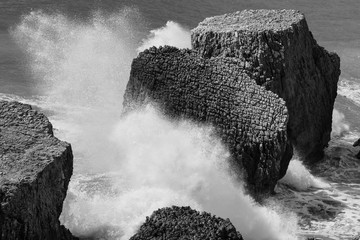 Large sharp rocks with lots of detail and texture  as waves splash forcefully against rocks