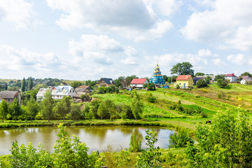 Landscape of farm green town and houses in summer in Rivne oblast village in Ukraine countryside during day with pond lake and church