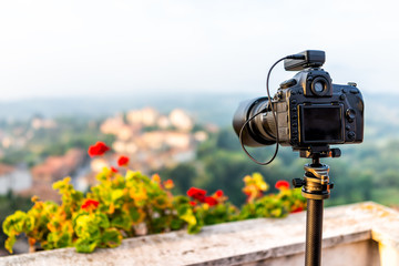 Chiusi Scalo sunset or sunrise of houses buildings in Tuscany, Italy with town cityscape and focus on dslr camera on tripod by flowers garden foreground
