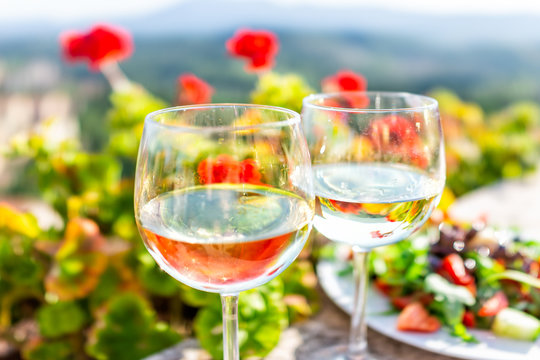 Macro closeup of two glasses of white wine and salad plate in garden with reflection in water of red geranium flowers outside in Tuscany Italy summer