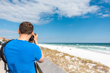 Destin Miramar beach city town village in Florida panhandle gulf of mexico ocean with photographer young man closeup in blue shirt taking picture photo of sand dunes with camera
