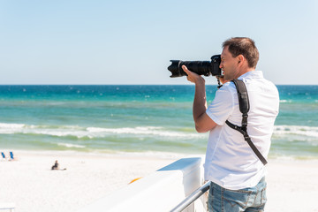 Young photographer man taking picture on beach during sunny day in Seaside, Florida panhandle town village with ocean by steps