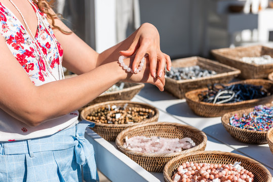 Young woman shopping for colorful stone beach bead bracelets trying on jewelry in outdoor market shop store in European, Greece, Italy or Mediterranean town village in summer
