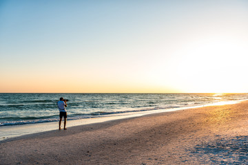 Young man professional photographer taking picture photo of beach sunset in Florida Siesta Key by Sarasota by beach waves holding big camera