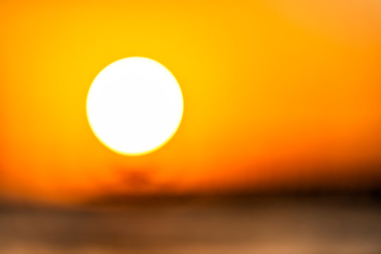 Bokeh blurry background abstract closeup of sun in Naples, Florida with orange sunset in gulf of Mexico and pier landscape on horizon