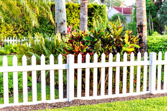 White beach wooden wood architecture picket fence of house in front porch yard garden with green landscaping trees vacation cottage home closeup