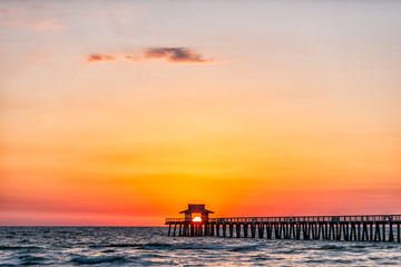 Fotobehang Napels Naples, Florida red pink and orange sunset skyscape in gulf of Mexico with sun setting inside behind Pier framing with horizon and ocean waves
