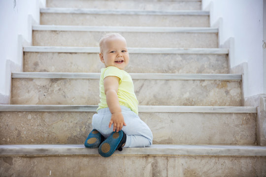 Happy baby girl crawling up stairs outdoors