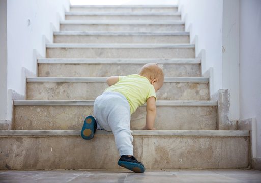 Baby girl crawling up stairs outdoors