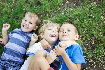 Three happy young boys lying down on grass in summer park