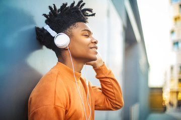 Cheerful guy listening music with the headphones