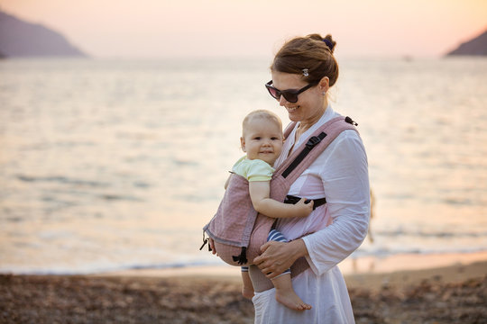 Cheerful Caucasian woman with little daughter in baby carrier on beach at sunset