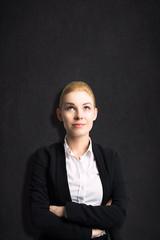 junge nachdenkliche Geschäftsfrau steht vor einer Wandtafel