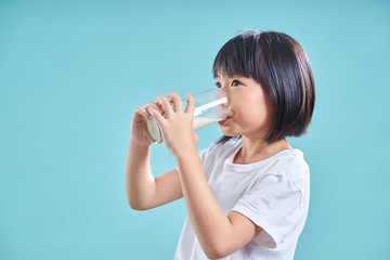 Asian little girl enjoy to drinking glass of milk isolated on light blue background  .