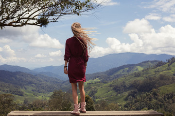 Young female enjoy, standing on tea plantations mountains view point
