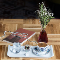Turkish Coffee with sweets and a book on table