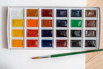 Watercolor paints and brushes, top view. Creative artistic mockup with copyspace.