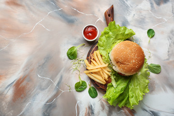 Tasty burger and french fries on table