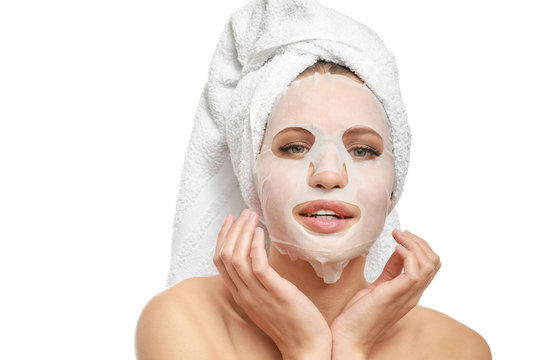 Beautiful young woman with sheet facial mask on white background