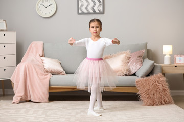 Cute little ballerina dancing at home