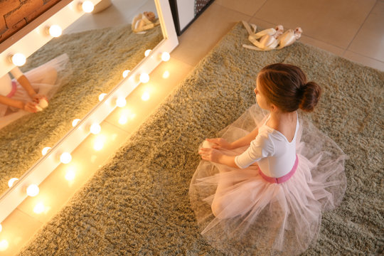 Cute little ballerina sitting in front of mirror at home