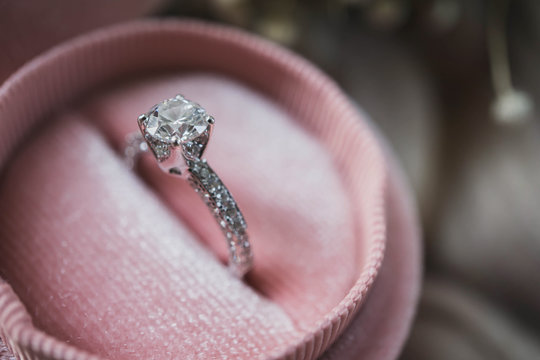 Close up of an elegant diamond ring in pink box. soft and selective focus. Love and wedding concept.