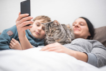 Familie mit Katze schaut ins Handy