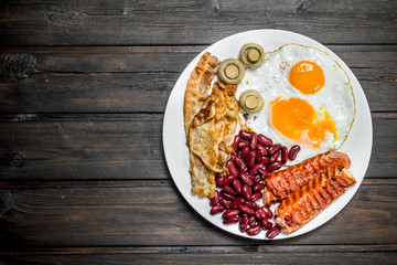 Traditional English Breakfast with fried eggs, sausages and beans.
