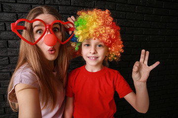 Woman and little girl in funny disguise on dark background. April fools' day celebration