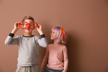 Little children in funny disguise on color background. April fools' day celebration