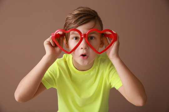Funny little boy with big glasses on color background