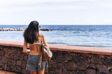 Pretty brunette long hair girl walking on the beach with black sand near sea.