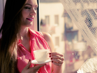 Woman looking through window, relaxing drinking coffee