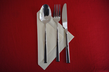 spoon, fork and knife on a paper napkin and a red tablecloth, table set with copy space, high angle view from above