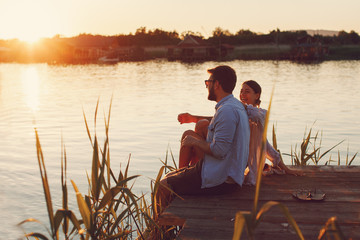 Young loving couple enjoys by the river during the sunset