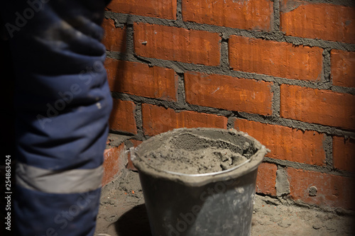professional construction worker laying bricks and building