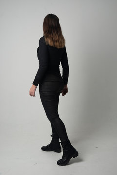 full length portrait of a brunette girl wearing  modern black jacket and pants, standing pose with back to the camera on grey studio background.
