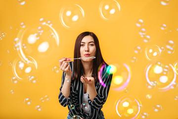 Pretty woman blows on soap bubble