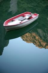 a small fishing boat on mountain lakes with a reflection of the sky