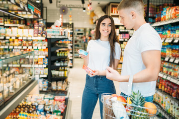 Young couple choosing products in supermarket
