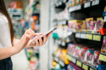Female customer with phone in hand, food store